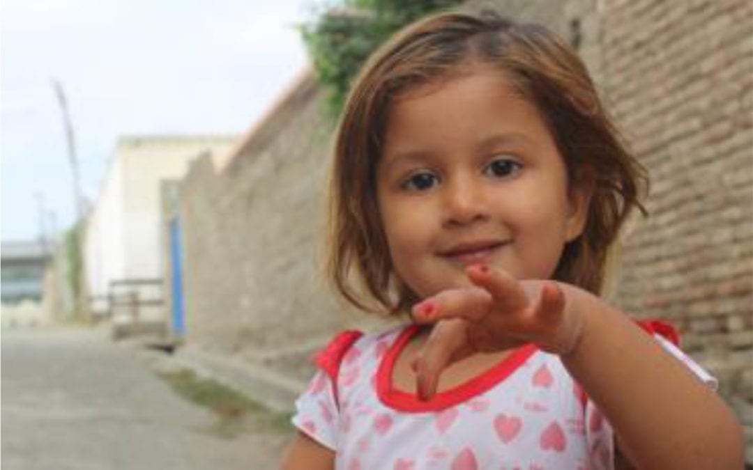 A child shows off her newly painted finger nails