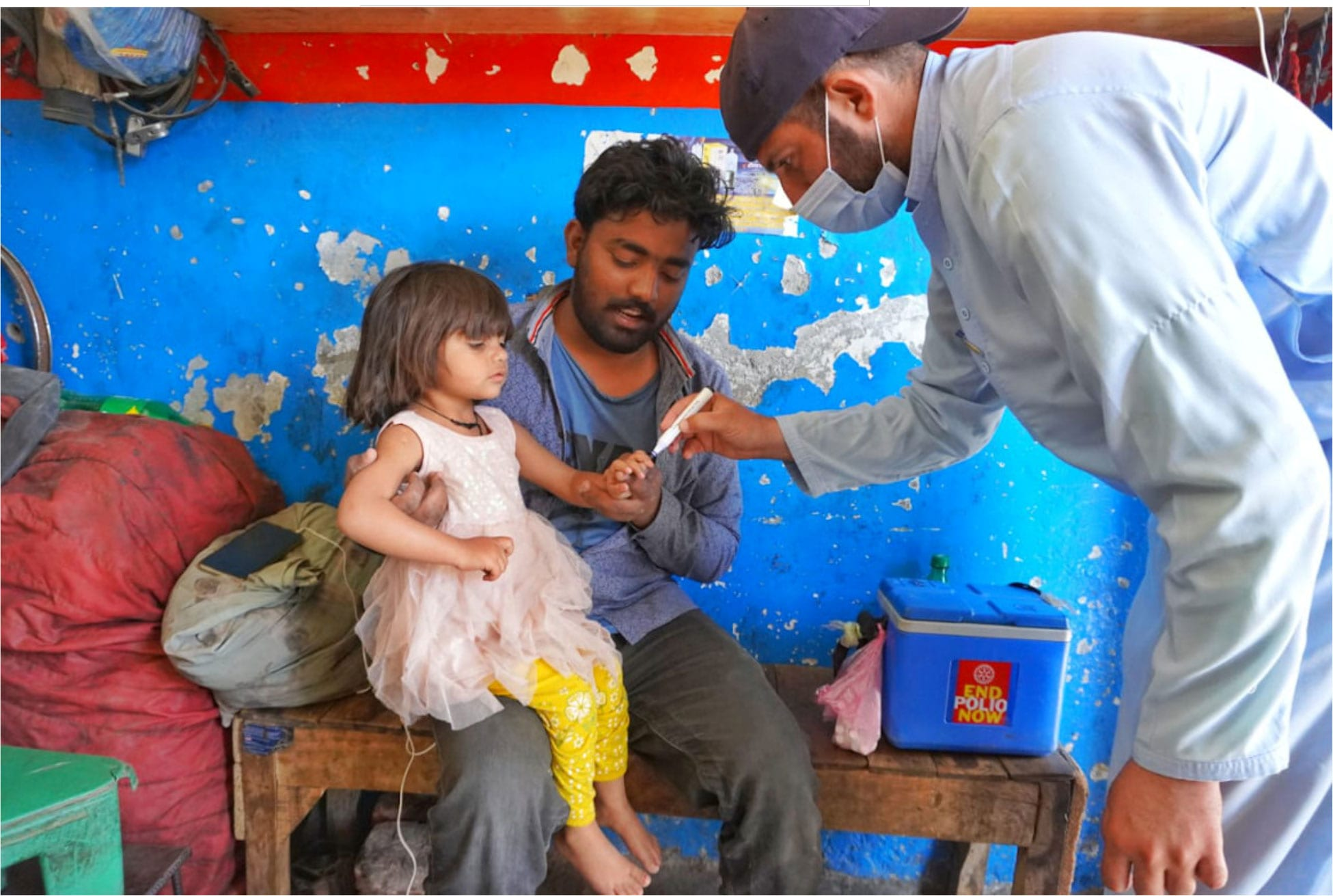 A vaccinator marking a vaccinated child